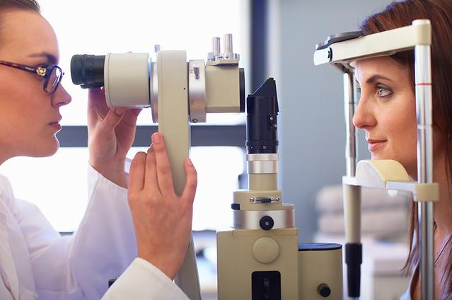 A side view of an Eye Care Professional and a young woman looking through a retinal camera