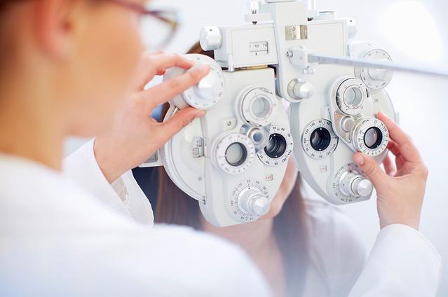 A young woman behind a phoropter as the Eye Care Professional checks her eyes during an eye exam