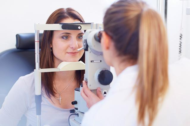 The camera focuses on a young woman looking through a retinal camera as her Eye Care Professional looks through the other side