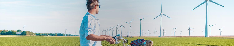 man watching windmills lower carbon emissions, carbon footprint